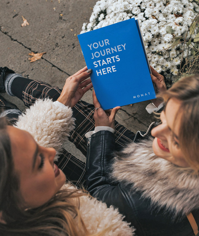 Picture of two women sitting on porch holding Your yourney starts here booklet