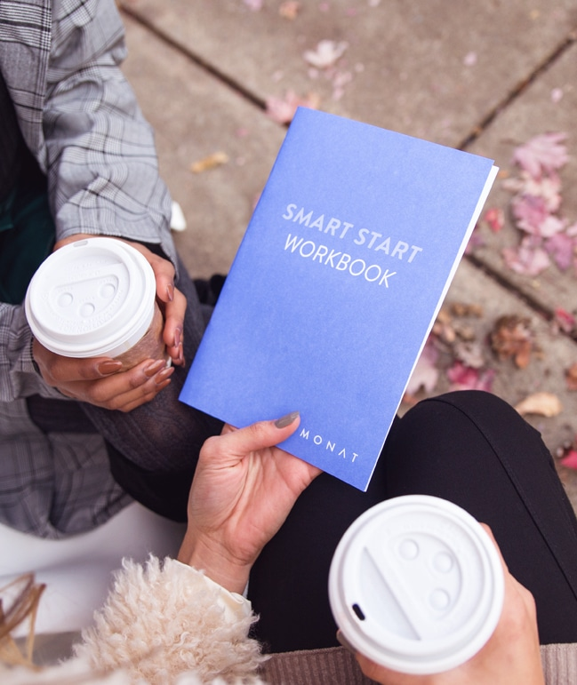 Picture of two women siting down having coffe holding Monat smart start workbook.