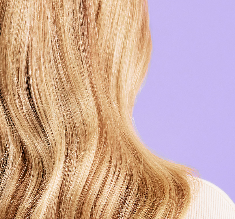 Back head shot of a blonde woman showing her results after treatment. Subject poses in front of a lavender       color background.