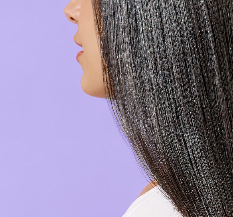 Closeup of a woman's brunette hair depicting smooth results. Subject poses in front of a solid,       lavender color background.