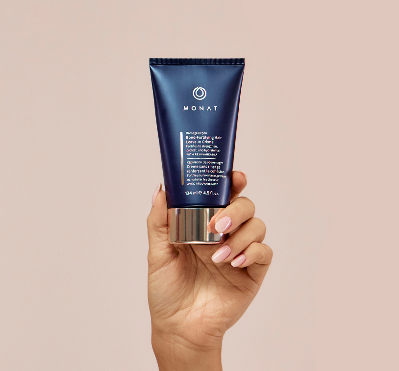 MONAT's ® Damage Repair Bond-Fortifying Hair Leave-In Crème being upheld by a woman's hand, showcasing the    product's aesthetics.