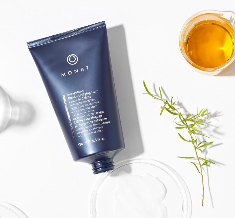 MONAT's ® Damage Repair Bond-Fortifying Hair Leave-In Crème lays over a solid white background exhibiting          its main ingredients such as oils & herbs placed along glass ornaments.